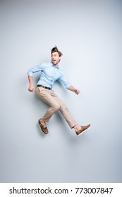 Happy, young, bearded, attractive handsome man in shirt, pants  jumping in air over grey background