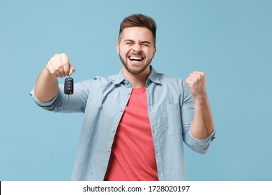 Happy young bearded guy 20s in casual shirt posing isolated on pastel blue wall background studio portrait. People emotions lifestyle concept. Mock up copy space. Hold car keys, doing winner gesture