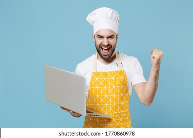 Happy young bearded male chef or cook baker man in apron white t-shirt toque chefs hat isolated on blue background in studio. Cooking food concept. Working on laptop pc computer, doing winner gesture