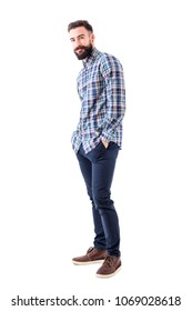 Happy young bearded man in checked shirt with hands in pockets smiling and looking at camera. Full body isolated on white background.