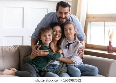 Happy young bearded man cuddling sitting on cozy couch beautiful wife with small daughter and son. Smiling loving full family posing for photo in living room at home, good relationship concept.