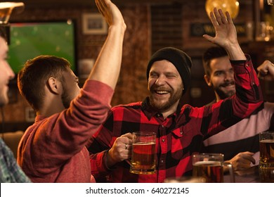 Happy young bearded man laughing high fiving his friend while having beer at the pub together watching football game mood celebration friendship happiness positivity success enjoyment relax entertain