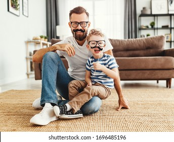 Happy young bearded man with little son having fun and playing with fake mustache while sitting together on sofa at home