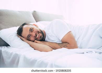 Happy young bearded man is relaxing on the bed at home