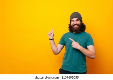Happy young bearded man in t-shirt pointing away over yellow background