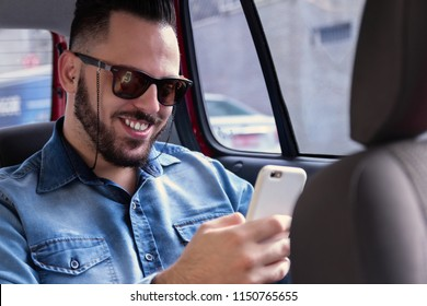 Happy young bearded man wearing denim shirt and sunglasses riding with transportation network company and holding cellphone in private vehicle transportation. Concept commute, aspirations, city life