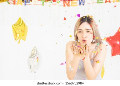Happy young beautiful Asian female blowing a colorful, shiny glitter, confetti in the new year party. background with copy space.