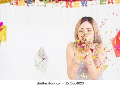 Happy young beautiful Asian woman blowing a colorful, shiny glitter, confetti in the new year party. background with copy space.