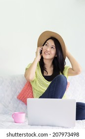 Happy young beautiful asian woman using smartphone with laptop on bed indoor.