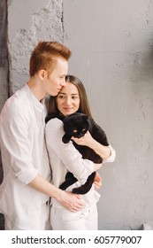 Happy young beautiful caucasian couple hugging and holding a cat. Playing with pet at home.