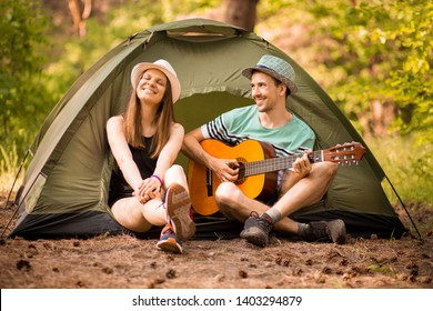 Happy young beautiful couple sitting with guitar in forest at tent. happy man confesses his love.