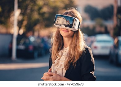 Happy young beautiful girl gesture testing virtual reality 3D video glasses VR headset dressed in a office outfit impressed by augmented reality on the street and beautiful autumn sun light colors