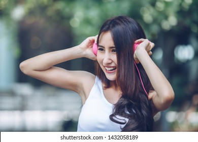 Happy young beautiful girl listening to the music with her pink headphones and dancing in the urban park