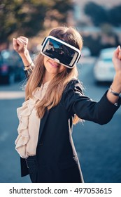 Happy young beautiful girl testing her virtual reality 3D video glasses VR headset dressed in a office outfit amused by augmented reality on the street and beautiful autumn sun light