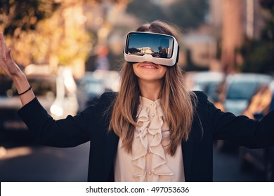 happy young beautiful girl testing virtual reality 3D video glasses VR headset dressed in a office outfit amazed by augmented reality on the street with beautiful autumn sun light colors