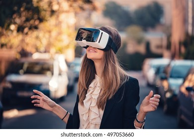 happy young beautiful girl testing virtual reality 3D video glasses VR headset and gesture dressed in a office outfit impressed by augmented reality on the street and beautiful autumn sun light colors