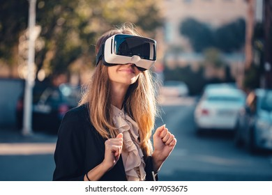 Happy young beautiful girl wearing virtual reality 3D video glasses VR headset dressed in a office outfit impressed by augmented reality on the street and beautiful autumn sun light colors