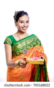 Happy young beautiful Indian woman in traditional saree with gift