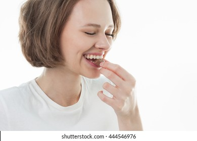Happy young beautiful lady eating chocolate and smiling. Big lips. Girl tasting sweet chocolate, short haired young woman with natural make up  having fun and eating chocolate candy