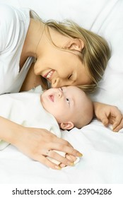 happy young beautiful mother on the white sofa with her baby