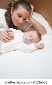 happy young beautiful mother on the bed with her sleeping baby