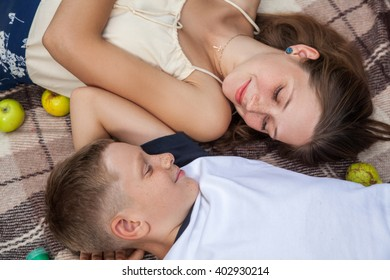 Happy young beautiful sister and brother with freckles on their faces posing lying down on plaid and smiling and looking at each other.