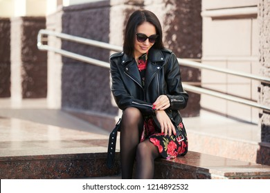 Happy young beautiful woman in city street Stylish fashion model wearing black leather jacket and sunglasses