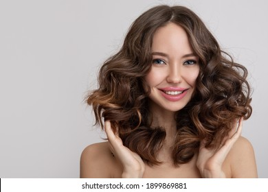 Happy young beautiful woman with curly hair. grey background