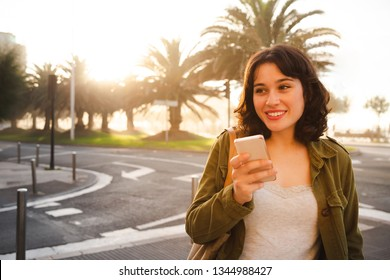 Happy young beautiful woman in green jacket talking on the phone walking on the city street at sunset