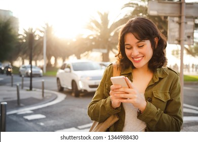 Happy young beautiful woman in green jacket using her smart phone walking on the city street at sunset
