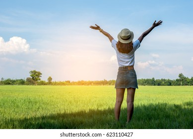 Happy young beautiful  woman in a green meadow.