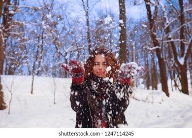 Happy young beautiful woman having fun with snow on a cold winter day.New Year, Christmas, winter and holyday concept.