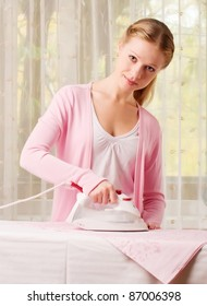 Happy young beautiful woman ironing clean clothes