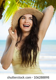 A happy young beautiful woman laughing and holding hat on a tropical beach with palm trees.