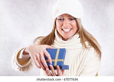 Happy Young Beautiful Woman Opening Christmas Gift/Smiling face/Ice background