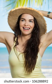 A happy young beautiful woman smiling and holding hat on a tropical beach.