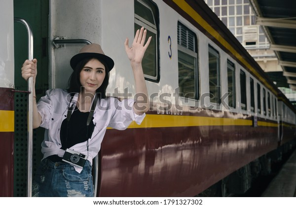 Happy young beautiful woman traveler holding camera and waving hello or goodbye standing on stairs vintage train, Business travel holiday relaxation concept