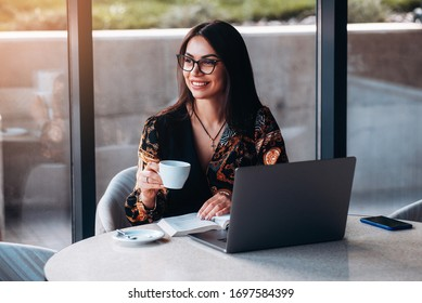 Happy Young Beautiful Woman Using Laptop and drink coffee. Business woman in a restaurant
