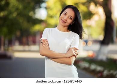 Happy young beautiful woman walking in city street Stylish fashion model wearing white t-shirt