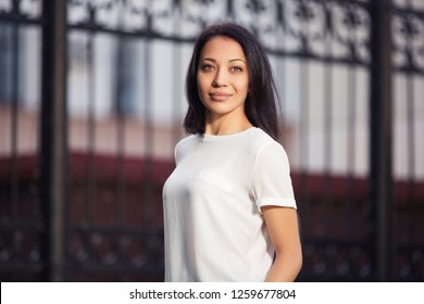 Happy young beautiful woman walking on city street Stylish fashion model with bob hair wearing white t-shirt