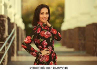 Happy young beautiful woman walking on city street Stylish fashion model with bob hair style in red floral print dress