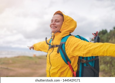 happy young beautiful woman in a yellow jacket windbreaker with a hiking backpack on the shore of the North Sea