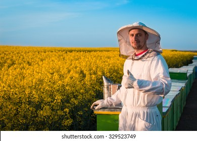 Happy young beekeeper working in the field of yellow flowers