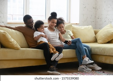 Happy young biracial parents relax on comfortable couch with little kids have fun watch video on smartphone together, african American family rest on sofa in living room using cellphone with children