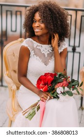 Happy young black bride smiling with bouquet of red flowers and sitting on vintage terracotta chair