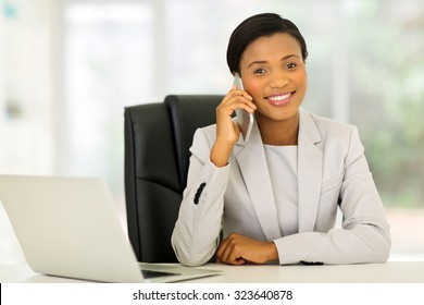 happy young black business woman talking on cell phone in office