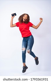 a happy young black lady jumping in excitement and holding a phone