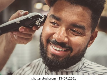 Happy young black man being trimmed with electric clipper machine in barbershop.Male beauty treatment concept.Smiling young African guy getting new haircut in barber salon