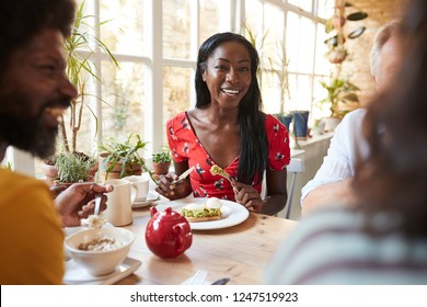 Happy young black woman eating brunch with friends at a cafe