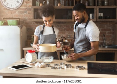 Happy young black woman and man baking pie in loft kitchen